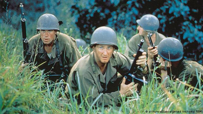 Four soldiers with guns crouch in high grass, film still from 'The Thin Red Line' (picture-alliance/United Archives/ TBM)