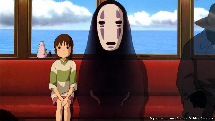 Scene from an animated film, girls sits on bench next to person with a huge mask and a black cloak (picture alliance/United Archives/Impress)