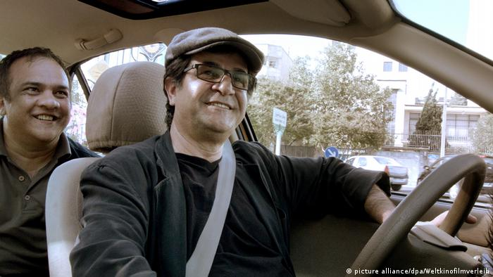 Two smiling men sit behind each other in a car (picture alliance/dpa/Weltkinofilmverleih)