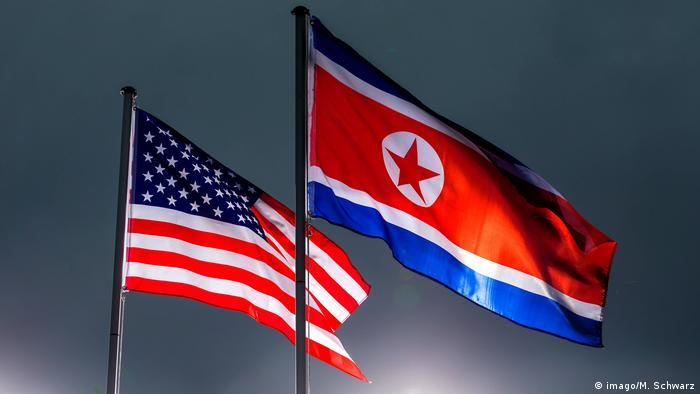 Флаги США и КНДР на фоне туч