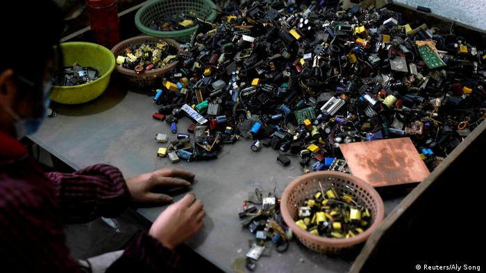 Photo: A person dismantling electronics (Source: Reuters/Aly Song )