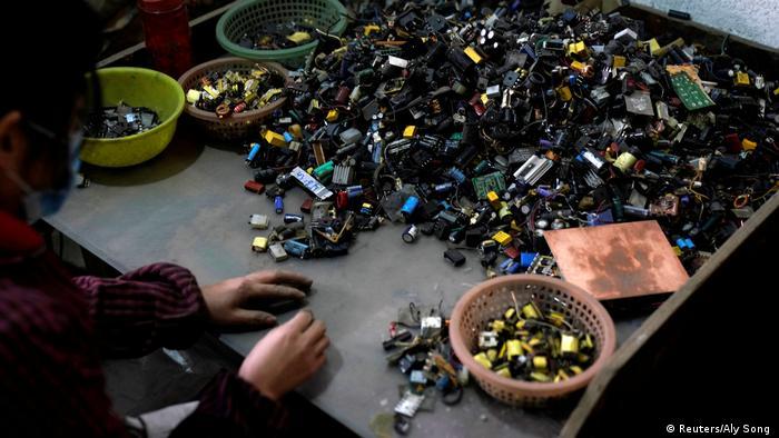 Una persona recicla las pequeñas piezas de aparatos electrónicos.