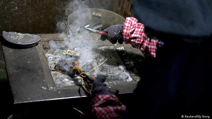 Photo: A worker burns hardware to get to precious metals