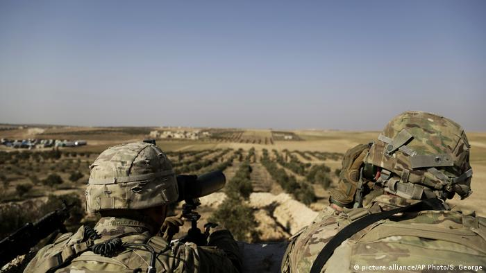 Two US soldiers gaze out over a dry Syrian landscape