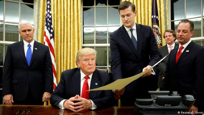Rob Porter hands a seated president Trump a document (Reuters/J. Ernst)