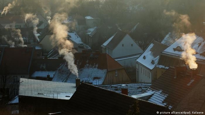 A cluster of houses where smoke billows from chimneys