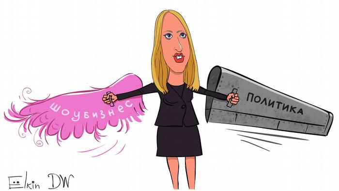 Карикатура - Ксения Собчак держит в каждой руке по крылу. В одной - из розовых перьев с надписью Шоубизнес, в другой - железное с надписью Политика.