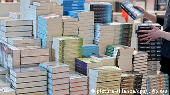 Books piled high on a table (picture-alliance/dpa/J. Woitas)