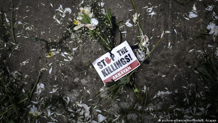 A flower with a sign that says 'Stop the killings' is seen on the ground following the funeral of a victim of the 'drug war'