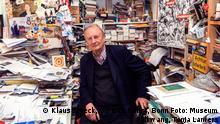 Klaus Staeck sitzt in einem Büro, das von Papieren überquillt (Klaus Staeck, VG Bild-Kunst, Bonn Foto: Museum Folkwang, Tanja Lamers)