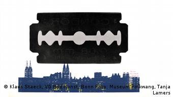 Plakat zur Essener Staeck-Ausstellung Sand fürs Getriebe Eine schwarze Rasierklinge über der Silhouette einer Stadt.