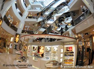 Ein Parfümerieladen in einem modern gestalteten Kaufhaus, darüber Rolltreppen