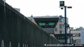 Outdoor view of Tegel theater with high wall and camera