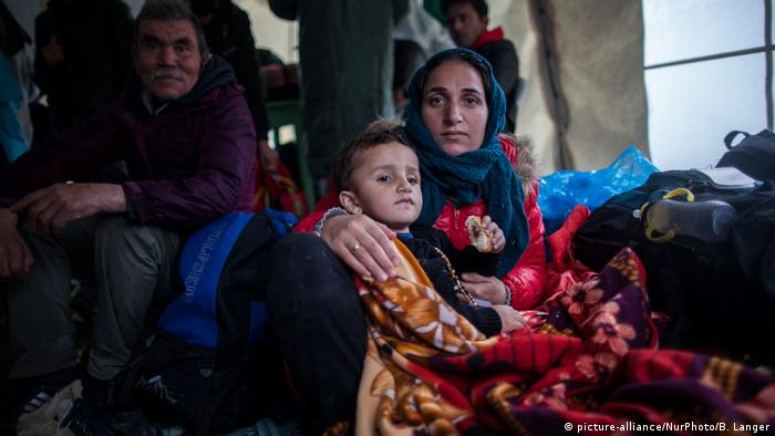 A woman and a boy are brought to the Moria refugee camp on Lesbos