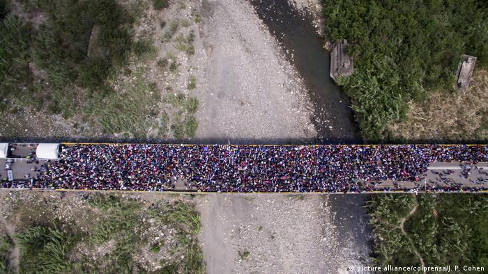 People flood over a bridge as vewed from above (picture alliance/colprensa/J. P. Cohen)