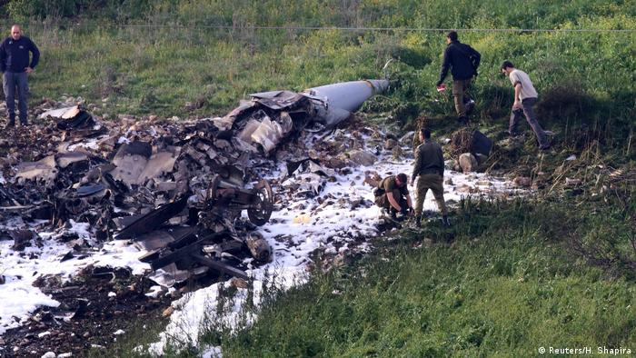 Israeli security forces walk next to the remains of an F-16 Israeli war plane