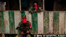 Members of Western Front of War Omar Gomez of the National Liberation Army (ELN) guerrilla, stand in a house on November 19, 2017 in the banks of the San Juan river, department of Choco, Colombia. Colombia's landmark peace deal with Marxist FARC rebels was supposed to mean peace for all but it has made little difference to indigenous and Afro-Colombian minorities, Amnesty International said on November 22, 2017. Although the agreement between the Colombian government and the FARC was signed, armed conflict is still very much the reality for millions across the country, said Salil Shetty, Secretary General at Amnesty International. / AFP PHOTO / LUIS ROBAYO / TO GO WITH AFP STORY (Photo credit should read LUIS ROBAYO/AFP/Getty Images)