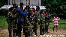 Members of Western Front of War Omar Gomez of the National Liberation Army (ELN) guerrilla, in line on November 20, 2017 in banks of the San Juan river, department of Choco, Colombia. Colombia's landmark peace deal with Marxist FARC rebels was supposed to mean peace for all but it has made little difference to indigenous and Afro-Colombian minorities, Amnesty International said on November 22, 2017. Although the agreement between the Colombian government and the FARC was signed, armed conflict is still very much the reality for millions across the country, said Salil Shetty, Secretary General at Amnesty International. / AFP PHOTO / LUIS ROBAYO / TO GO WITH AFP STORY (Photo credit should read LUIS ROBAYO/AFP/Getty Images)