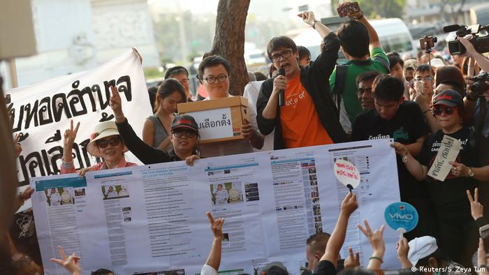 Pro-democracy activists in Bangkok hold up placards
