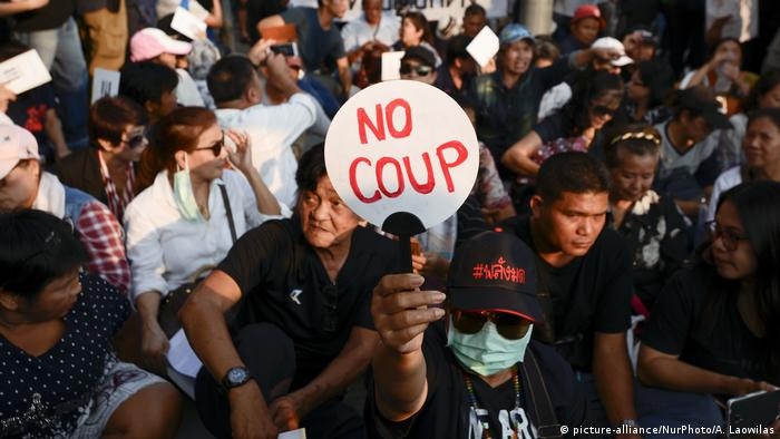 A protester in Thailand holds a sign saying 'no coup'