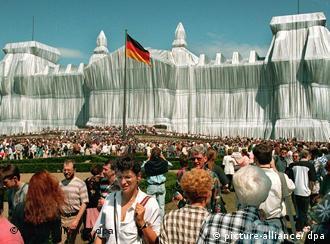 Viele Menschen vor dem mit Stoff verhüllten Reichstagsgebäude