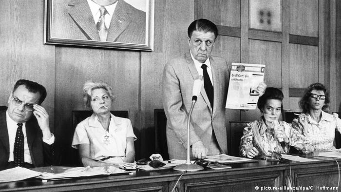 A black-and-white photo of a press conference, with four people sitting and one man standing, holding a document in his hand.