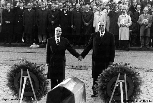 French President Francois Mitterand and German Chancellor Helmut Kohl stand hand-in-hand at the 1984 World War One commemoration ceremony in Verdun