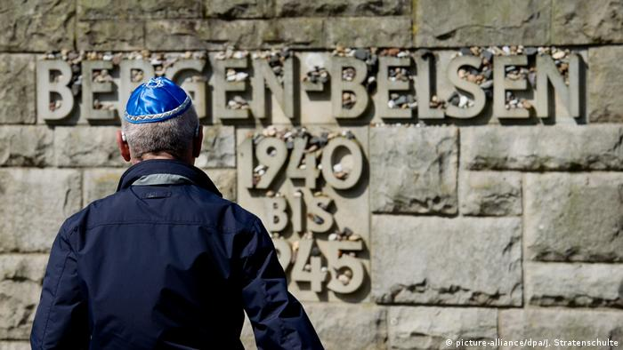 A Holocaust survivor stands in front of a memorial at the Bergen-Belsen memorial