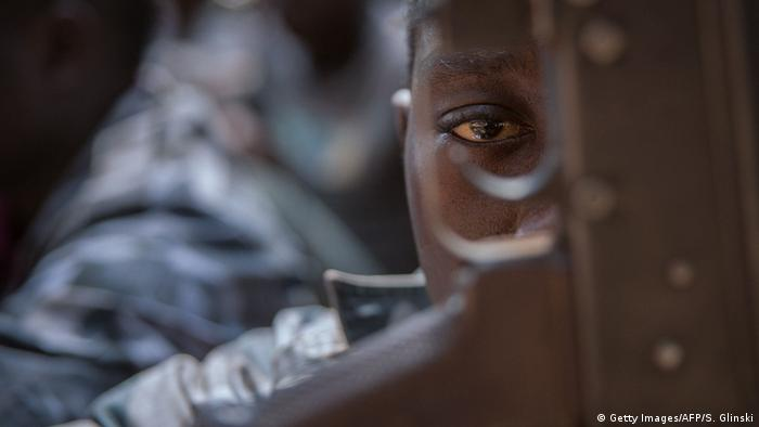 Child soldier looking through rifle trigger guard