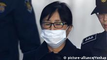 Choi Soon-sil heads to a Seoul courthouse with her mouth covered with a white mask