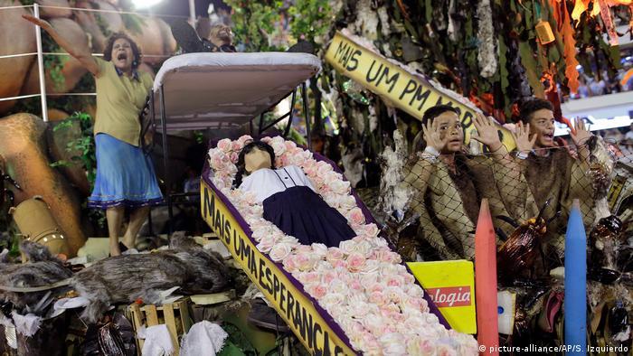 Carro alegórico da Beija-Flor de Nilópolis traz caixão com boneco que representa estudante morto, com críticas à violência, à intolerância e à corrupção