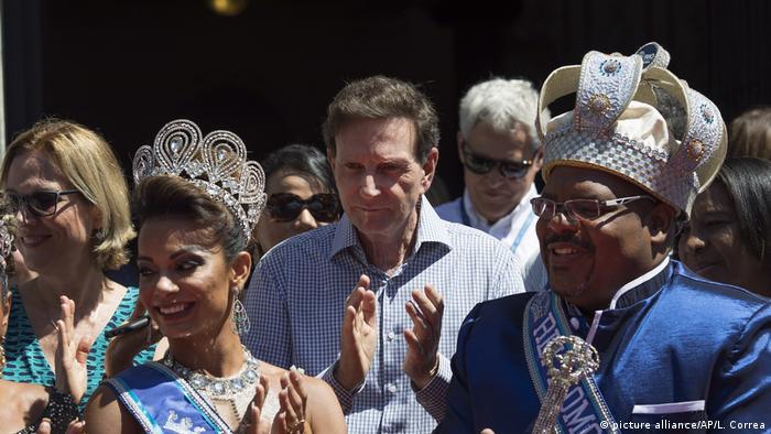 Entre a rainha Jéssica Maia (e.) e o Rei Momo de 2018, Milton Júnior (d.), o prefeito do Rio de Janeiro, Marcelo Crivella, aplaude durante cerimônia que marcou o início oficial do carnaval carioca