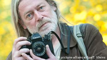 Fotógrafo Harald Hauswald segurando uma câmera fotográfica