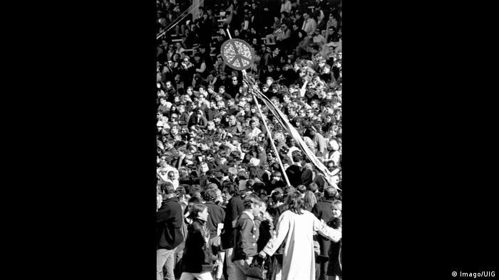 Peace-Zeichen an einem Holzstab befestigt ragt aus einer Menschenmenge. (Imago/UIG)