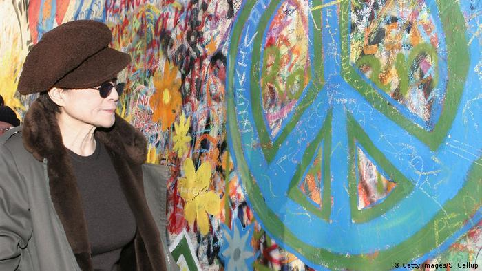 Yoko Ono betrachtet ein buntes Peace-Zeichen, das auf die Prager Lennon Mauer gemalt ist. (Getty Images/S. Gallup)