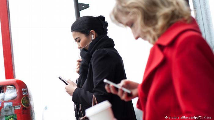 Frau telefoniert über eine Freisprecheinrichtung an der Bushaltestelle (picture alliance/dpa/C. Klose )