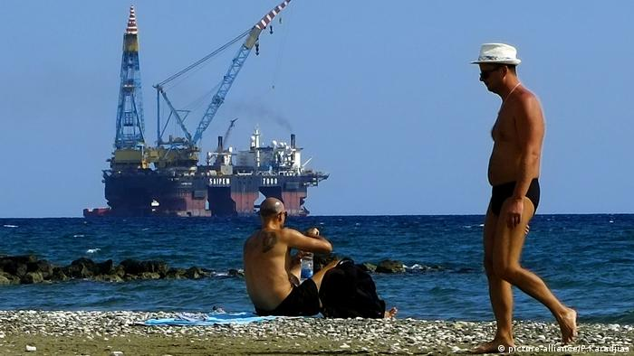 Two men sit on a beach in Cyprus with a drilling platform seen in the background