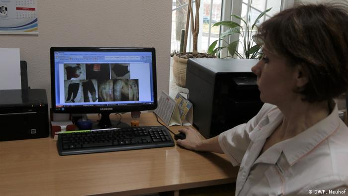 A hospital member of staff showing images of corpses on a computer