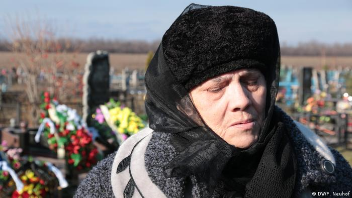A mother mourning her son at a grave in Ukraine