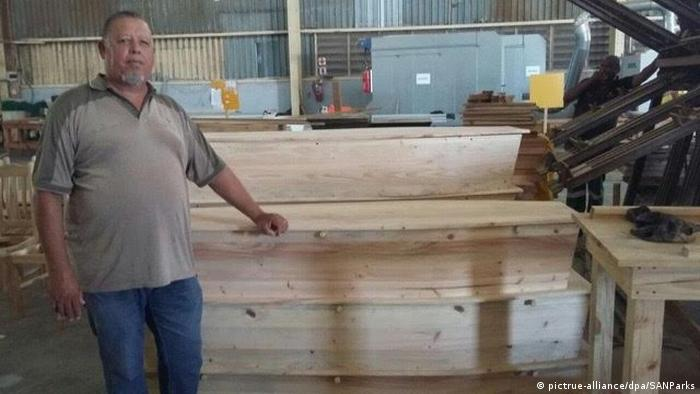 Eco Furniture factory manager Emile Mopp standing by some caskets (Source: SANparks)