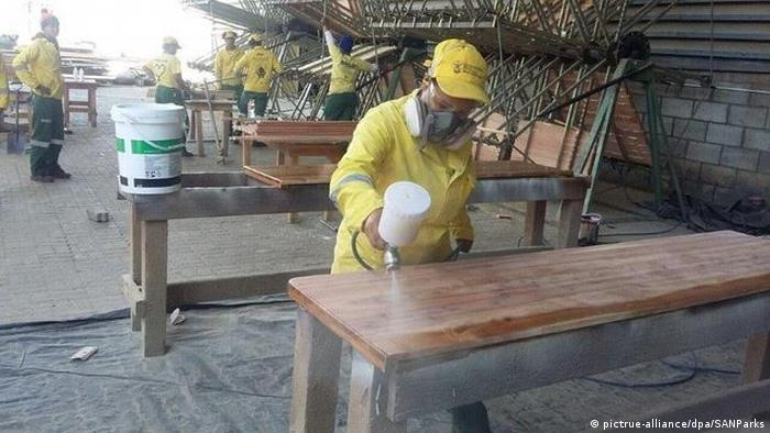 An employee at the Eco Furniture Factory in George, South Africa, sprays a casket