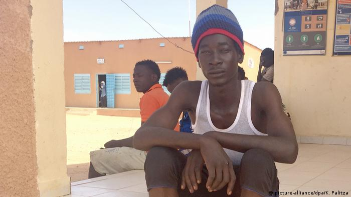 A young man sitting in the shade of the transit center building in Agadez