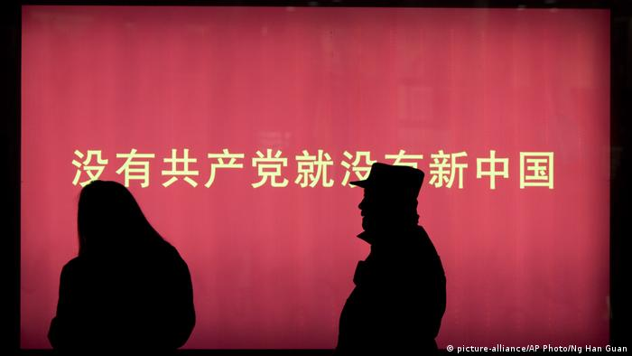 A silhouette of a man and a woman in front of a slogan: Without the Communist Party, there would be no China.