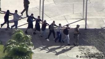 Alunos são escoltados para fora da escola durante o ataque