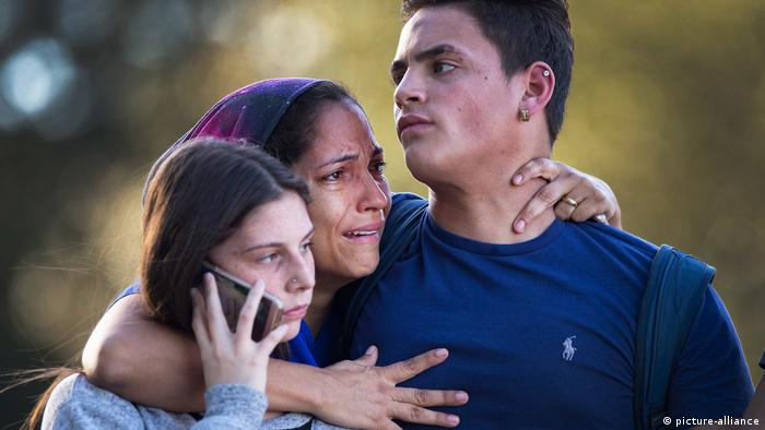 Students are consoled by a family member after a shooting at Stoneman Douglas High