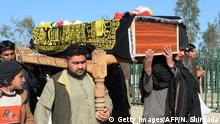 Afghan mourners carry the coffin of one of 18 victims of a bomb attack that targeted a funeral ceremony