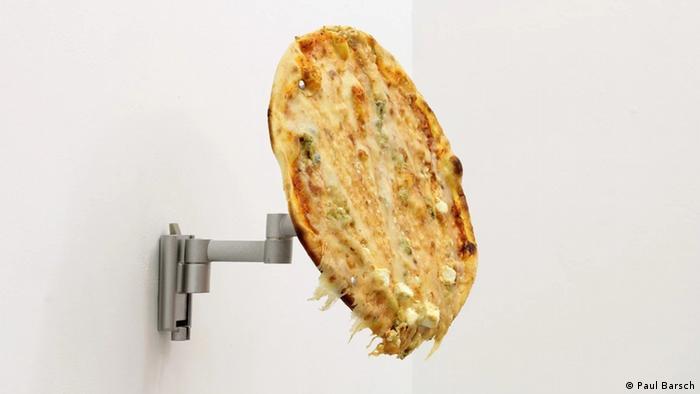 Eine Pizza, die mit einer Halterung an der Wand befestigt ist (Paul Barsch)