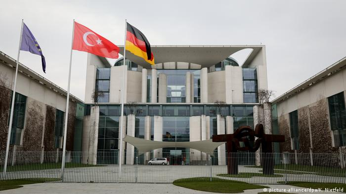 The Turkish flag flies between the EU and German ones outside the Chancellery