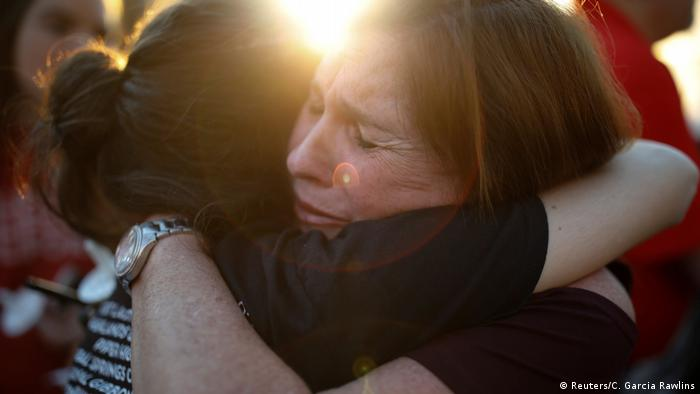 Women react during a candlelight vigil for victims of the shooting in Parkland, Florida