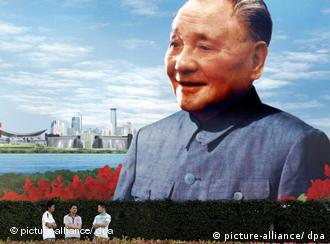 Tourists stand in front of a painting of the late leader of the Communist Party of China Deng Xiaoping